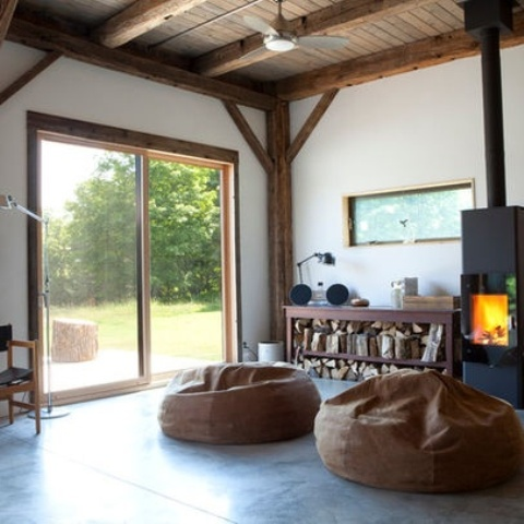 a modern and laconic fireplace and a wooden storage unit with firewood and with various objects on display for a modern and airy space