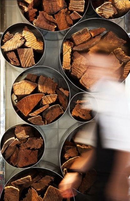a modern and laconic wall storage unit of metal pipes can be used not only for firewood but for other stuff, too, and is a decor feature at the same time