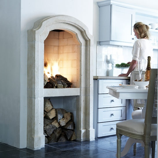 an arched vintage hearth and a built-in niche for firewood under it is a very cool way to make vintage look modern