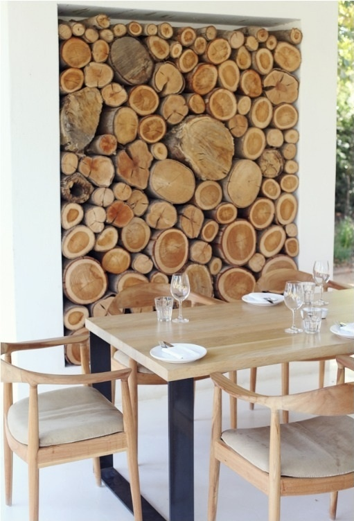 a niche with firewood as a decor feature for an outdoor dining room, to connect it to nature and make it look cozy