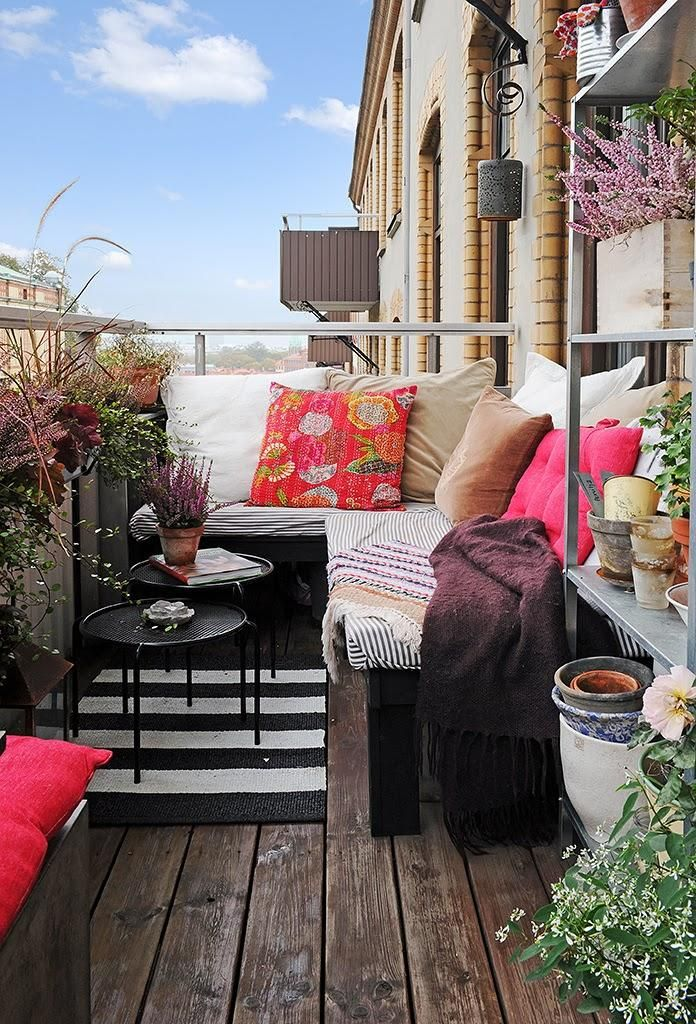 a bright summer balcony with a dark wooden floor, dark wooden furniture, potted greenery and blooms and bright textiles