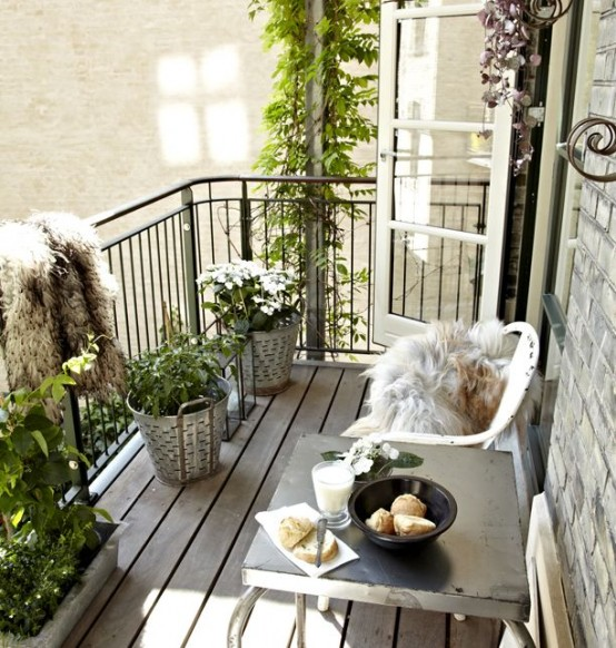 a neutral balcony for summer with potted greenery and blooms, metal furniture, faux fur covers for chairs