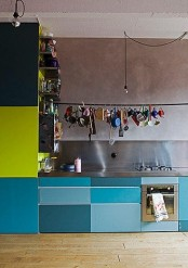 a creatively bright kitchen with bright and metallic blue cabinets and neon green parts, with a stainless steel backsplash and countertops is bold and cool