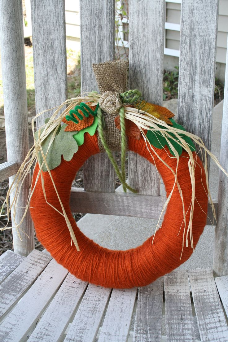a colorful fall wreath covered with orange yarn, with colorful fall leaves, fabric blooms and husks