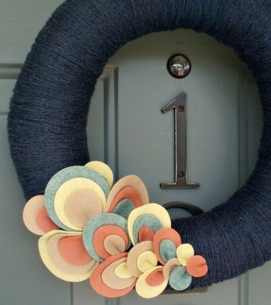 a contrasting fall wreath covered with black yarn and bright fabric leaves that decorate it