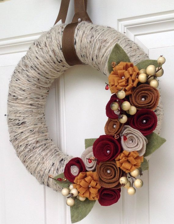 a fall yarn wreath covered with grey twine, with moody fabric flowers, leaves and faux berries for a more neutral look