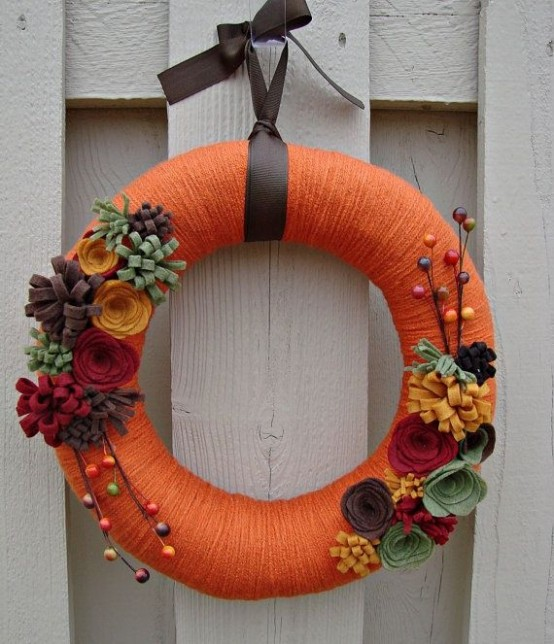 a colorful fall wreath with orange yarn, fabric blooms, berries and branches is a fun and playful idea