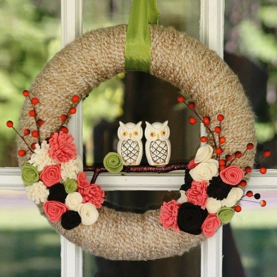 a fall wreath covered with grey yarn, with colorful fabric blooms, branches with berries and mini owls