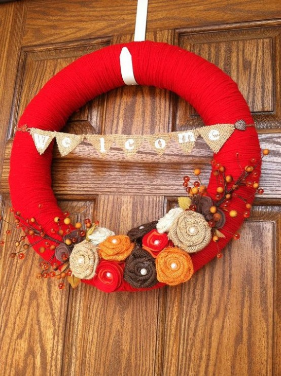 a bright fall wreath covered with red yarn, with bright fabric blooms, faux branches and berries is a fun idea