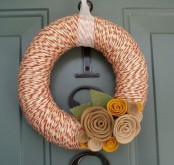 a bright yarn wreath covered with orange and white yarn for a pattern, fabric and burlap blooms and a ribbon