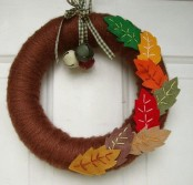 a bold fall wreath covered with brown yarn, with colorful fabric leaves and some bells is a fun and creative decoration