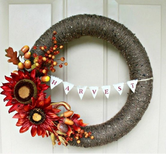 a dramatic fall wreath covered with dark grey yarn, with bright faux blooms, veggies, berries and leaves and a bunting