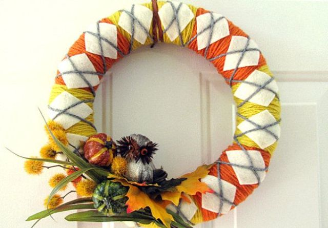 a colorful fall wreath with yellow and orange yarn, with white fabric rhombs, with faux leaves, veggies and dried blooms and a faux owl