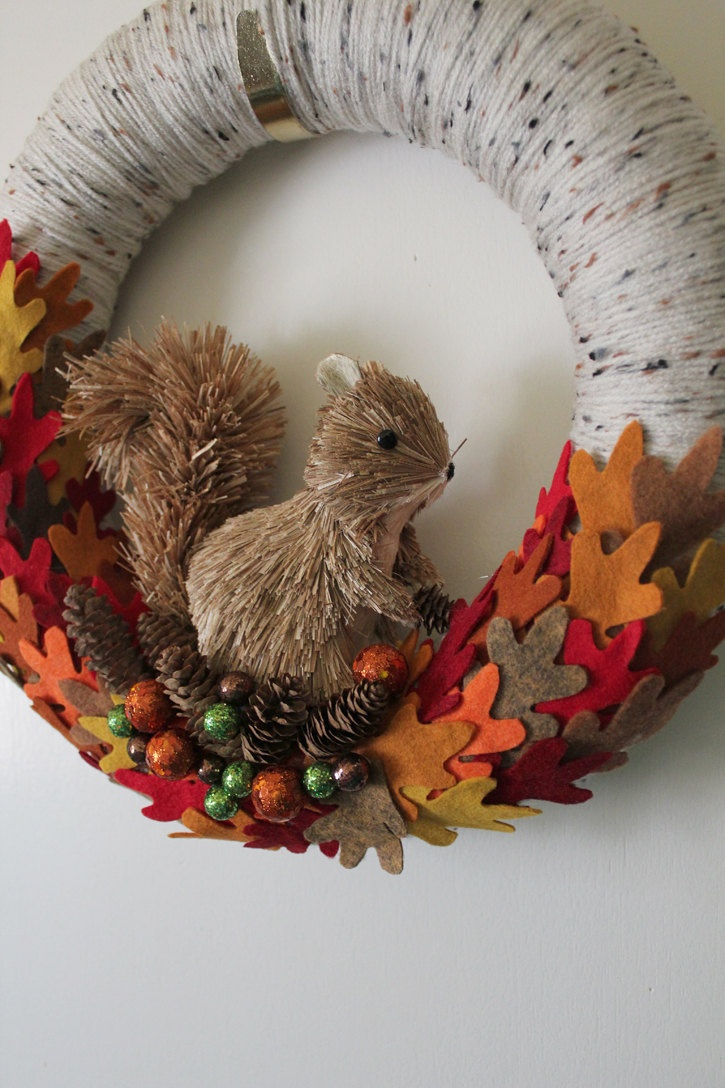 a bold fall wreath covered with grey yarn, with colorful fabric leaves, berries and a faux squirrel to add a woodland touch
