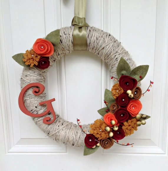 a bright and cool fall wreath covered with grey yarn, with fabric blooms, leaves and twigs and a monogram for a rustic feel