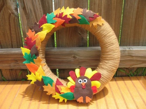 a bright fall wreath covered with twine, with colorful fabric leaves and a fabric turkey is a bold decoration