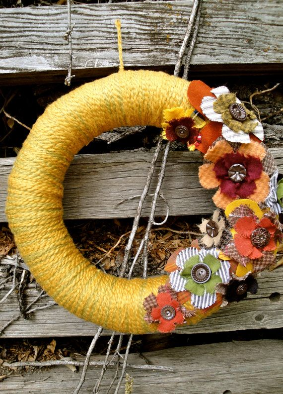a colorful yarn fall wreath with yellow yarn, fabric blooms and vintage buttons is a cool vintage decoration