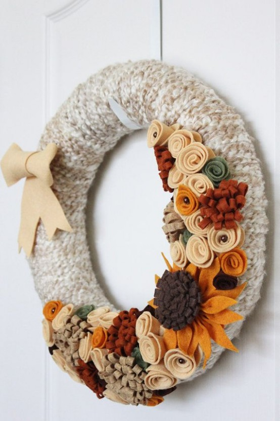 a fun fall wreath covered with grey yarn, with colorful fabric flowers and leaves and a bow for styling your front door