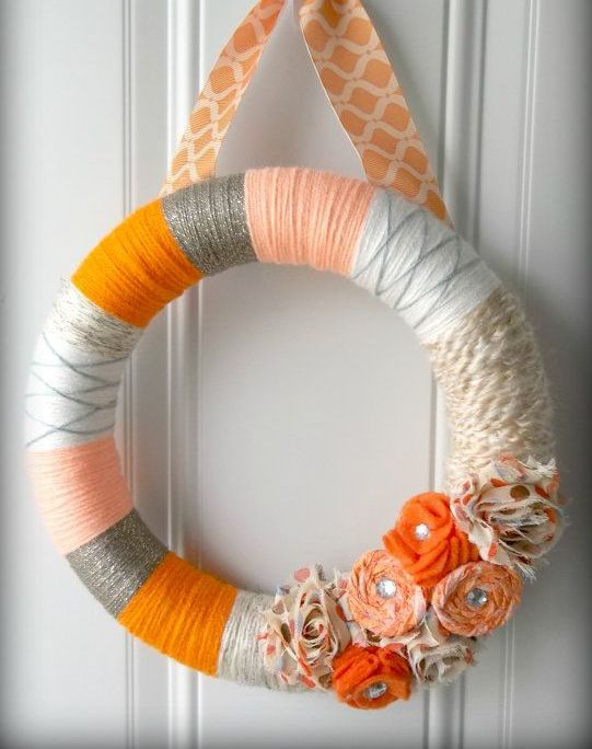 a colorful flal wreath covered with grey, orange, white yarn, with bright fabric blooms and a printed ribbon