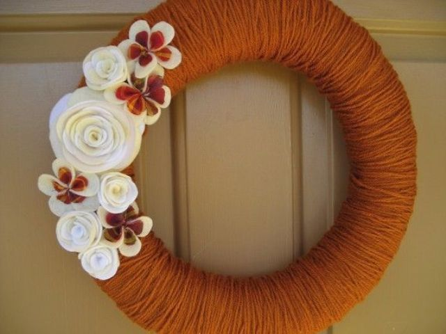 a bright fall wreath covered with rust yarn, with white and rust fabric flowers and beads is a truly fall colored idea