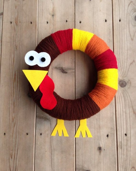 a fun toy-like wreath shaped as a turkey with yellow, red, burgundy and brown yarn and a head made of cardboard