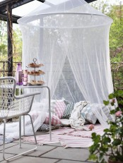 a terrace with a pillow space with rugs and a mosquito net over – invite your kids to spend time there without any bugs
