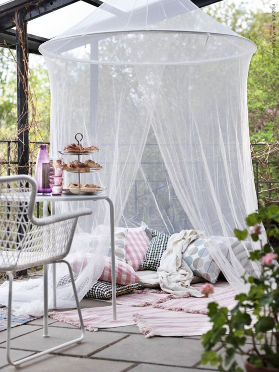 a terrace with a pillow space with rugs and a mosquito net over - invite your kids to spend time there without any bugs