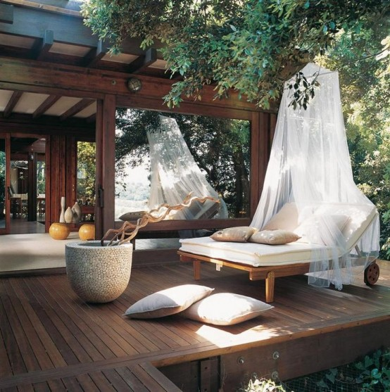 a relaxing zen terrace with a double lounger and a mosquito net for a more zen feeling and comfort