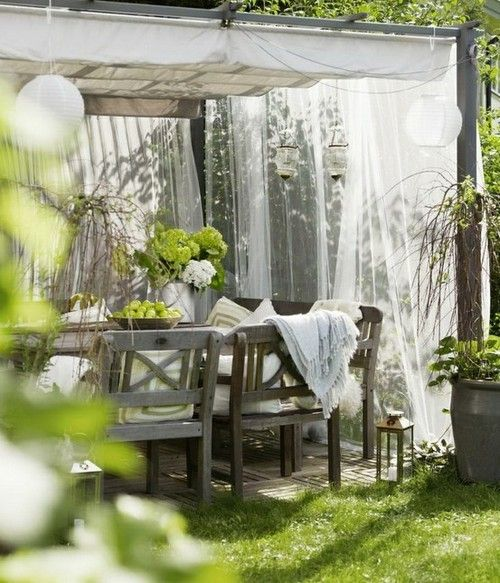 an outdoor rustic dining space with mosquito net curtains around that help to keep the space welcoming and comfortable