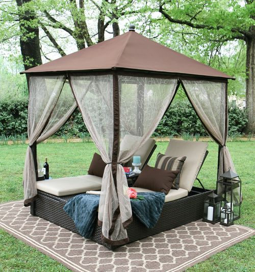a wicker double lounger with metal roof to keep rain away and mosquito curtains to avoid bugs