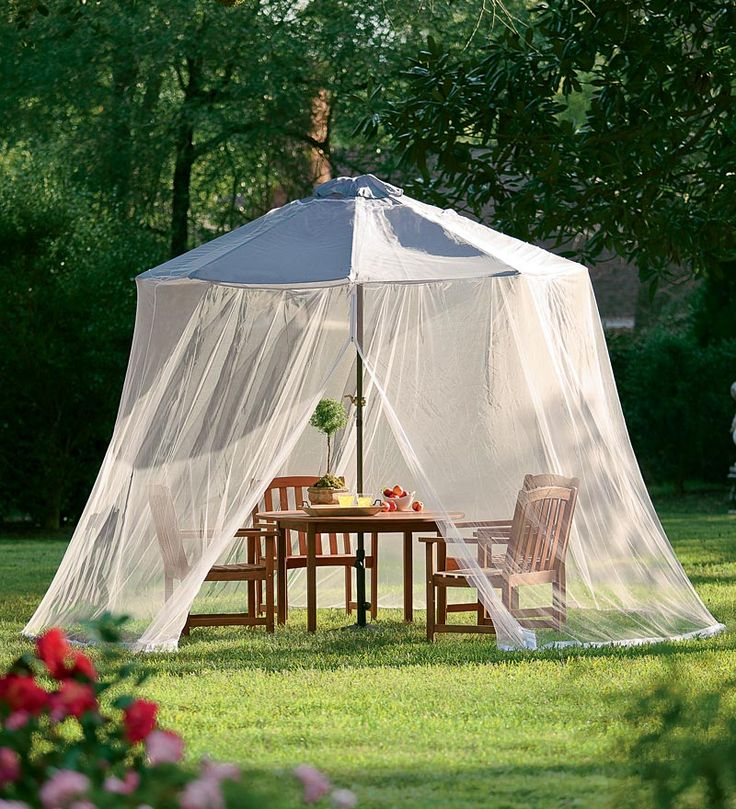 an outdoor rustic dining space covered with an oversized mosquito net with a tent helps to avoid sunshine, bugs and even rain