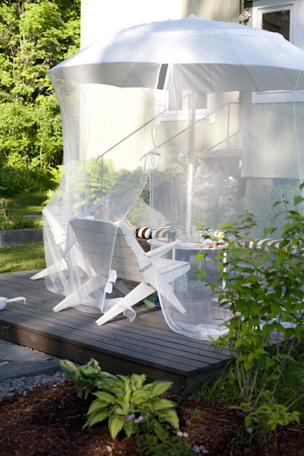 a comfortable sitting zone with chairs, a coffee table, an umbrella and a mosquito net over them all
