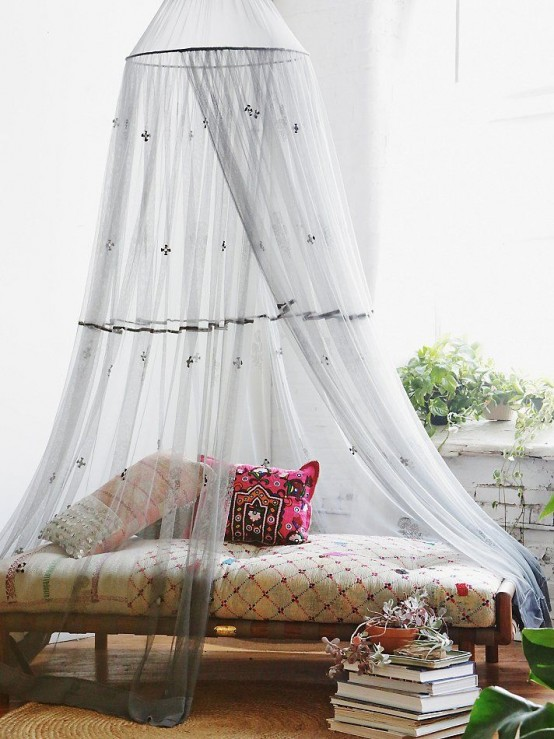 a boho daybed with an embroidered grey mosquito net that adds chic and decor value to the space