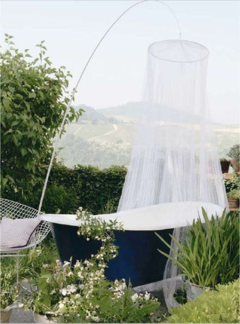 an outdoor navy bathtub with a mosquito net over it to highlight the tub and give it some privacy at the same time