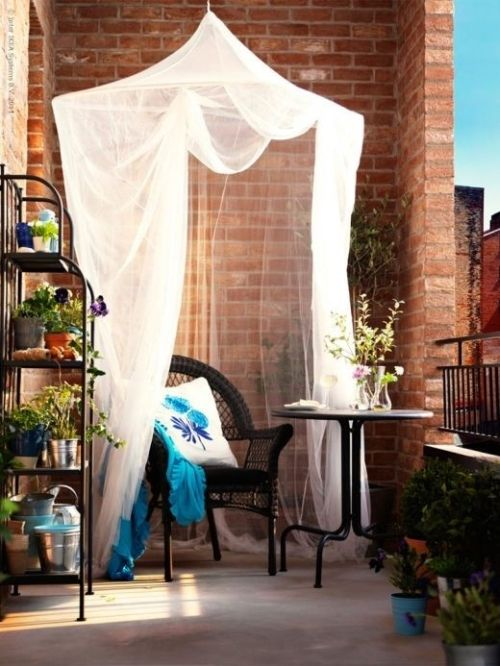 a mosquito net used for decor in a small balcony, it gives a relaxed feel to the red brick space