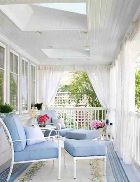 a beautiful porch done with light blue furniture and mosquito net curtains that can give privacy and save from bugs