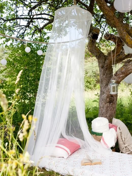 a daybed with a mosquito net over it, with pillows and lanterns to create your own outdoor oasis for relaxation