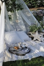 a cozy boho outdoor space done with a blanket, pillows and a mosquito net over the space