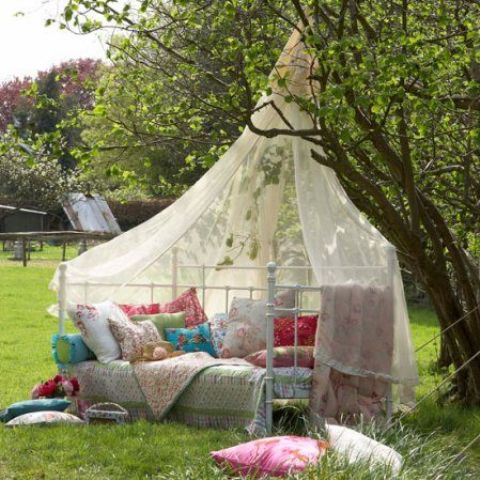 a boho chic daybed placed right in the garden with a mosquito net over it to keep bugs away