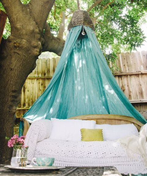 a wooden bench with boho lace bedding and a turquoise mosquito net over it to add color and style