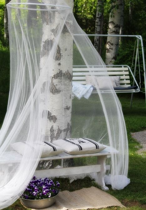 a bench with pillows and a mosquito net over it makes up a cozy and welcoming nook for relaxing