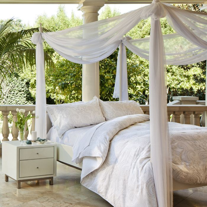 a bed placed outdoors and covered with mosquito net curtains and a canopy is a gorgeous idea for having a nap outside