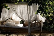 an outdoor daybed with canopy curtains and lots of pillows is a very relaxing idea to try