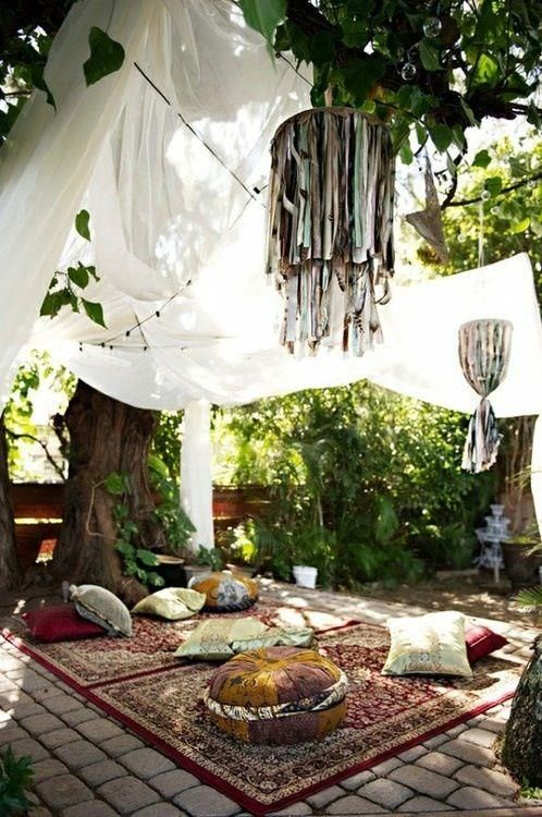 an outdoor boho space done with rugs, pillows, cushions and mosquito nets over it for a mood and vibes more than for bugs