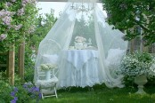 an outdoor dining space with chairs and a table plus a mosquito net over the whole space