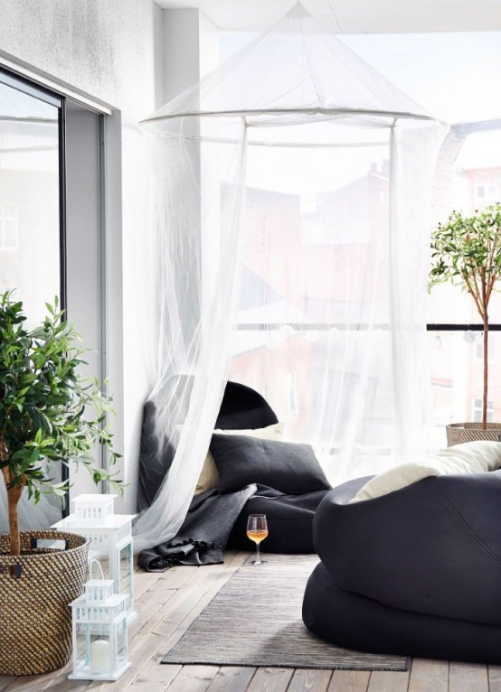 a contemporary balcony with black bean bag chairs and mosquito nets over them - both for decor and to avoid bugs