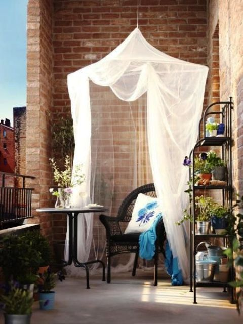 a small stting space on a balcony - a coffee table and a wicker chair covered with a mosquito net for more comfort