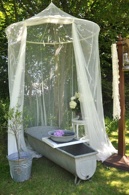 an outdoor metal tub with a mosquito net over it to avoid any bugs and keep some privacy at the same time