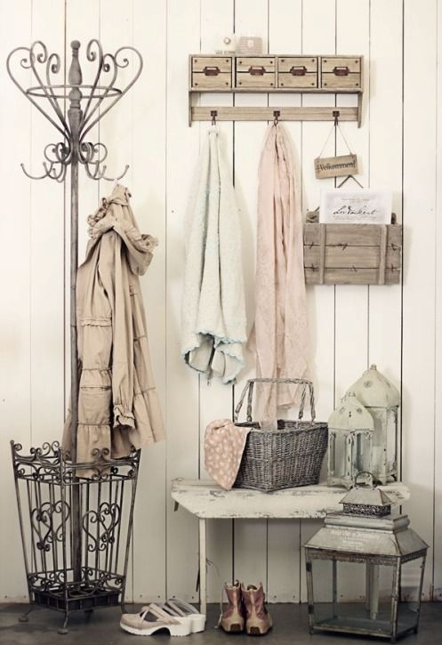 a simple shabby chic entryway with clothes hangers and a holder, a bench, candle lanterns and a basket for storage