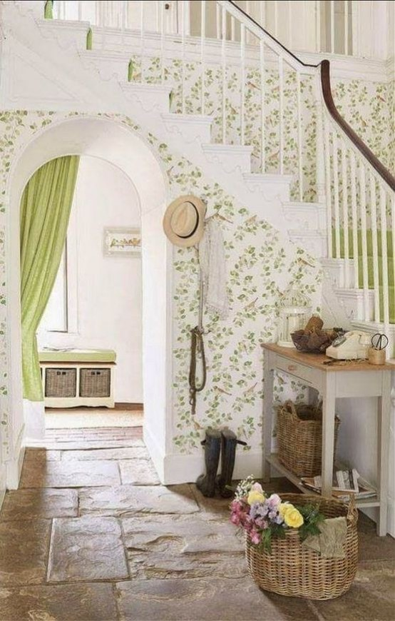 a cute neutral and green entryway with printed wallpaper, a console table, baskets and a storage bench with baskets